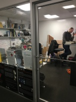 a graduate student crammed in a locked, but fully transparent, corner office