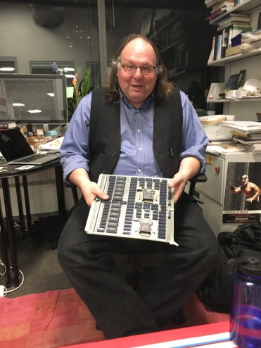 Ethan Zuckerman, Director of the Center for Civic Media, posing with a handwired circuit board he found under the floorboards