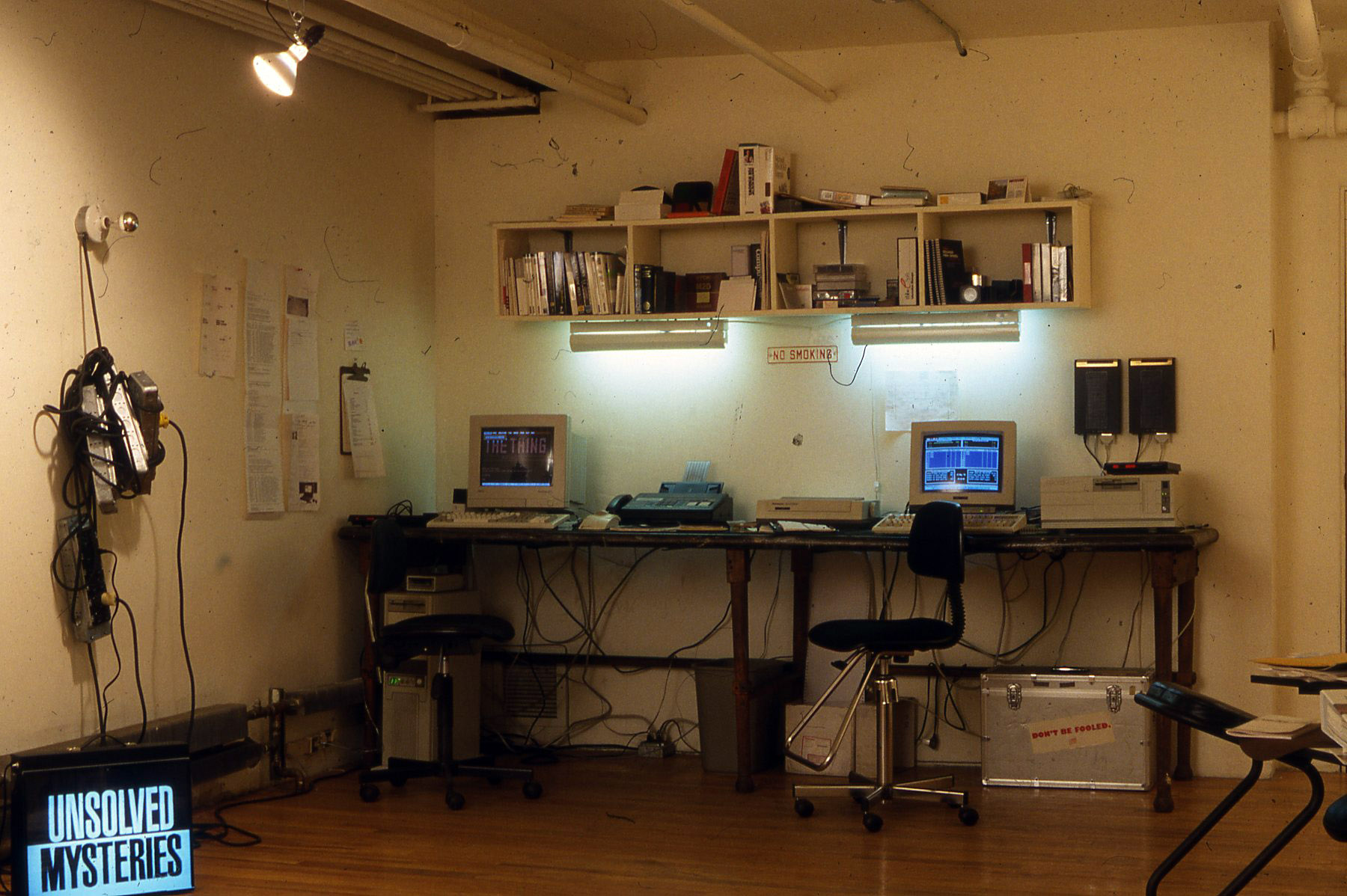 an open office area featuring a desk and two computers from the 1990s